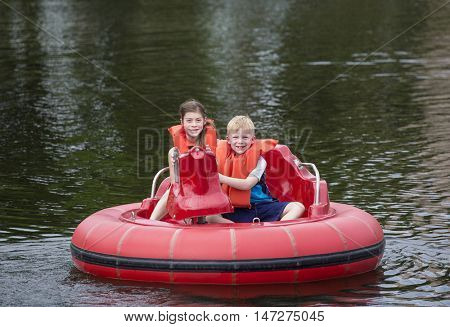 Cute kids having fun riding bumper boats on a lake