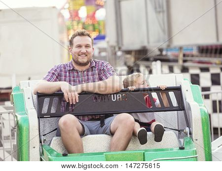 Smiling father and son on an Amusement Park Ride together
