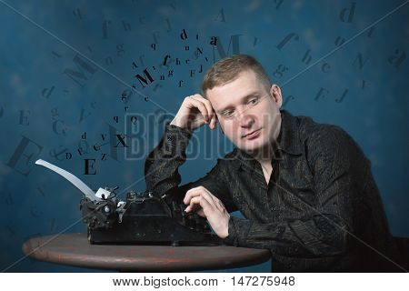 Man writer sits at a table in front of a typewriter