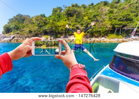Smartphone photographing Asian young man jumping in the water Similan Island Koh Ta Chai Andaman Sea Thailand