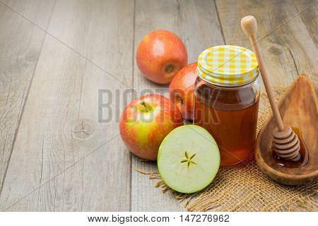Apple and honey jar on wooden background. Jewish Rosh hashana (new year) celebration