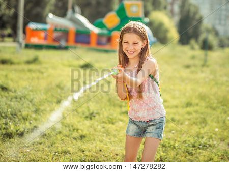 little joyful girl playing with water gun outside
