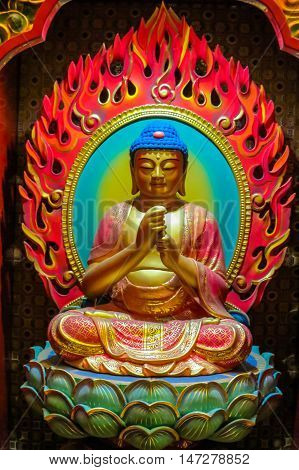 Buddha image that is carved of wood. Buddha sitting in a lotus flower and his hands is in various positions mudras.