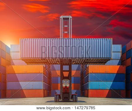Forklift truck lifting cargo container in shipping yard for transportation import export and colorful sunset sky background