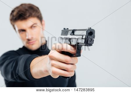 Closeup of focused young man standing and aiming with gun