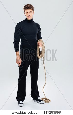 Full length of serious young man burglar with rope and gun