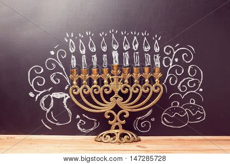 Creative Jewish holiday Hanukkah background with menorahl over chalkboard with hand drawing