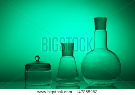 Laboratory glassware on color background on the table.