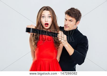 Cryminal man covering mouth of scared young woman with tape