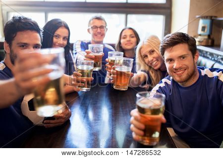 sport, soccer, people and leisure concept - happy friends or football fans clinking beer glasses and celebrating victory at bar or pub