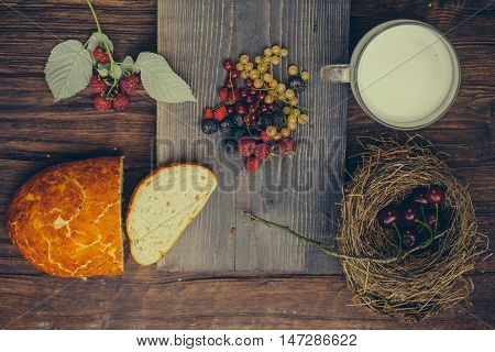 Freshly baked loaf of wheat bread and cut slice on wooden board with red and white currant strawberry cherry blackberry raspberry and glass cup of milk
