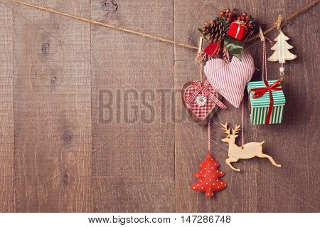 Rustic Christmas decorations hanging over wooden background with copy space