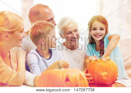 family, happiness, generation, holidays and people concept - happy family making halloween pumpkins at home