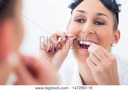 Woman wearing eye mask in bathroom cleans teeth with dental floss