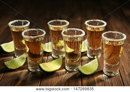 Gold tequila shots in a row with lime slices and salt on wooden background