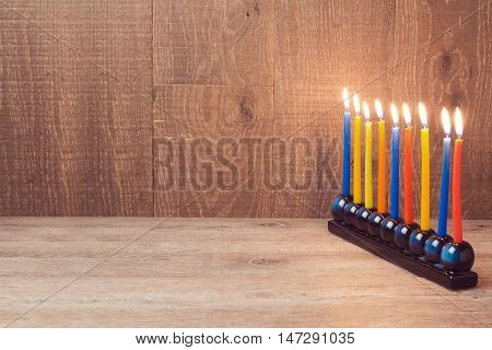 Jewish Holiday Hanukkah menorah with colorful candles over wooden background