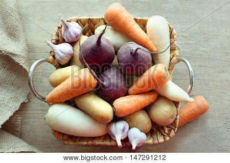 Root vegetables in basket on wooden table