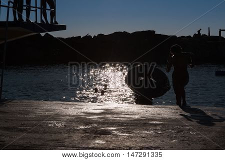Silhouette Of Children Playing Board In The Summer With Water