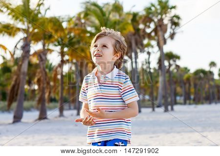Adorable active little kid boy having fun on Miami beach, Key Biscayne. Happy cute child smiling and laughing at the camera and having dreams.