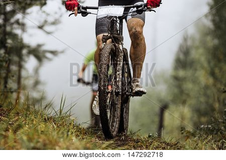 closeup wheel mountainbike and feet rider in spray of dirt. riding in autumn forest