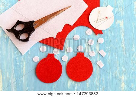 How to make a felt Christmas decoration. Tutorial. Step. Cut pieces of felt for Christmas ball decoration. Scissors, white and red felt scraps on blue wooden background. Top view
