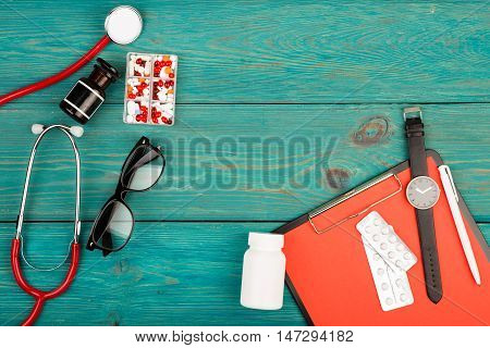 Stethoscope, Clipboard, Watch, Glasses And Pills On Blue Wooden Desk