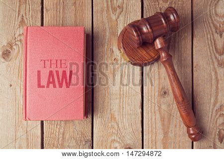 Law book and gavel on wooden background. Justice concept
