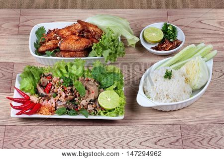 Sticky rice served with fried chicken and spicy sour chicken salad on wood. Side view.