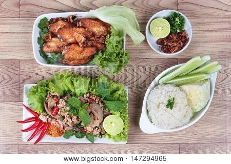 Sticky rice served with fried chicken and spicy sour chicken salad on wood. Top view.