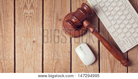 Law gavel and keyboard on wooden background. Online law enforcement concept. View from above