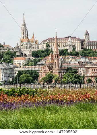 Matthias church Fishermans bastion and Calvinist church in Budapest Hungary. Cultural heritage. Architectural theme. Vertical composition. Greenery in the park.