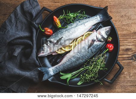 Raw uncooked seabass fish with lemon slices, herbs and spices on black grilling iron pan over rustic wooden background, top view,