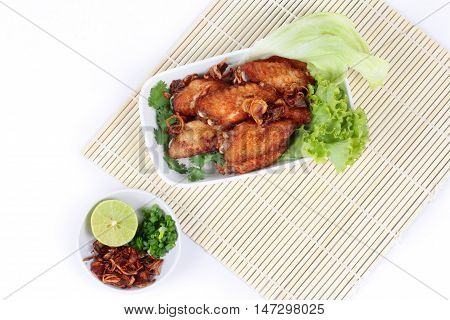 Deep fried chicken topped fried sliced red onion served with side dish as halve green lemon ,minced shallots and filled fried red onion on bamboo and white. Top view.