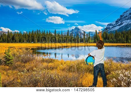 Curious boy with a globe under his arm.  Beautiful nature of the Rocky Mountains of Canada