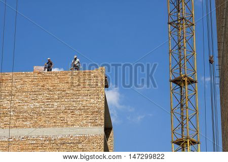 Building brick block wall on construction. Construction mason worker bricklayer making a brickwork