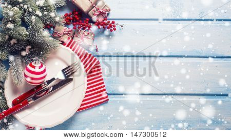 Christmas table setting. White plate knife and fork napkin and christmas decorations in white and red colors on blue wooden table. Top view. Drawn snow. Selective focus. Place for text.