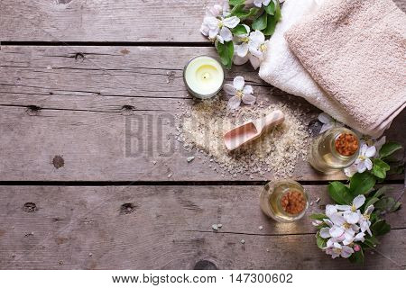 Spa setting. Sea salt bottles with aroma oil towels and flowers on aged wooden background. Selective focus. Place for text.