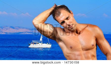 Young man  by the sea with a sailing ship passing behind him