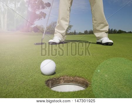 Man putting golf ball on green