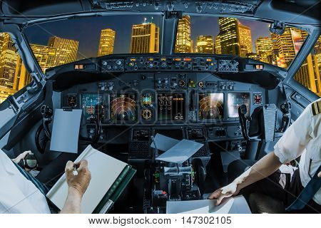 Cockpit and board of an airplane at night with pilots arms and blank white papers for copy space