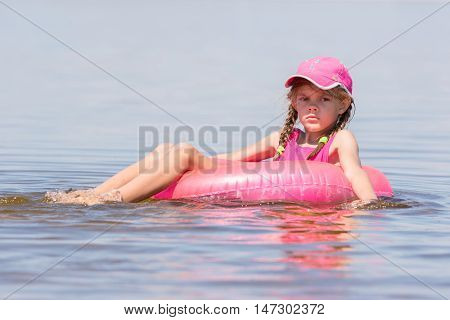 Sad Girl In A Cap Floating In The River Sat On The Swimming Circle