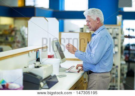 Pharmacist making prescription record through computer in pharmacy
