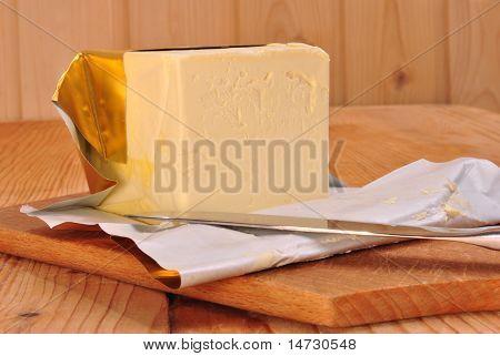ein Cube Margarine und einem Küchenmesser