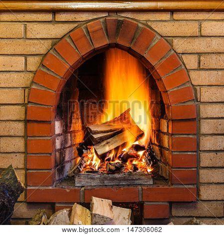 Wood Burning In Indoor Brick Fireplace