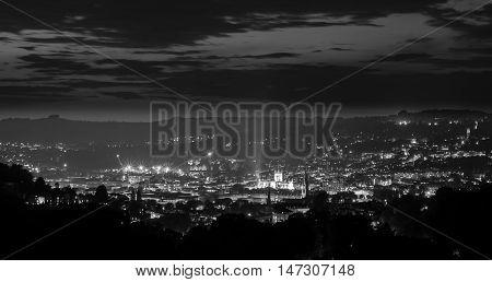 Panorama of Bath Abbey and city at night from above. High view of UNESCO World Heritage site with streetlights in black and white in Somerset England UK
