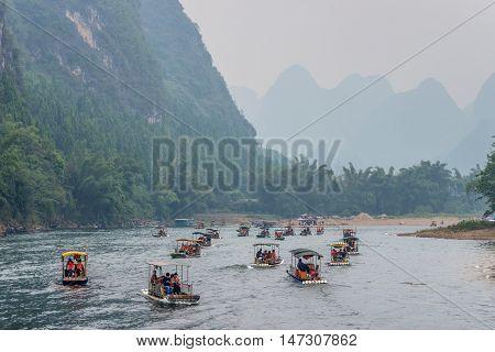 Yangshuo China - October 20 2013: Many Bamboo Rafts on the Li river in the haze near Yangshuo China.