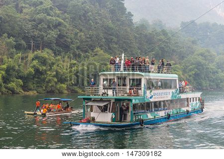 Yangshou China - October 20 2013: A tourist boat packed with tourists travels the magnificent scenic route along the Li river from Guilin to Yangshou.