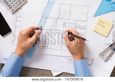 Top view of architect drawing new project on blueprint. Closeup of man hands working and sketching a construction project on office desk. Project of new house.