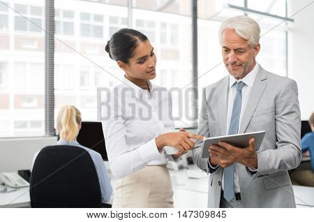 Senior businessman taking help from assistant on operating digital tablet. Assistant showing manager changes made in presentation. Senior leadership and multiethnic businesswoman working at office.