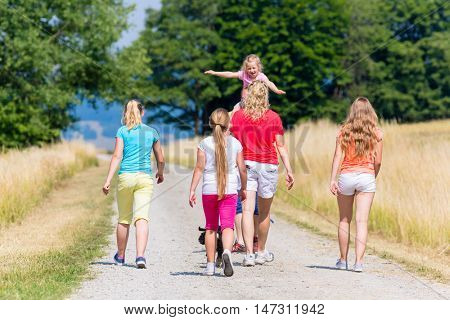 Family, mother father and kids, having walk in summer on dirt path